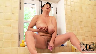 Huge-titted brunette milf teases herself while taking a soapy bath